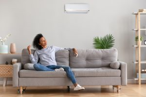 African american relaxed woman sitting on comfortable couch in living room at modern home holds air conditioner remote control enjoying breathing fresh air.